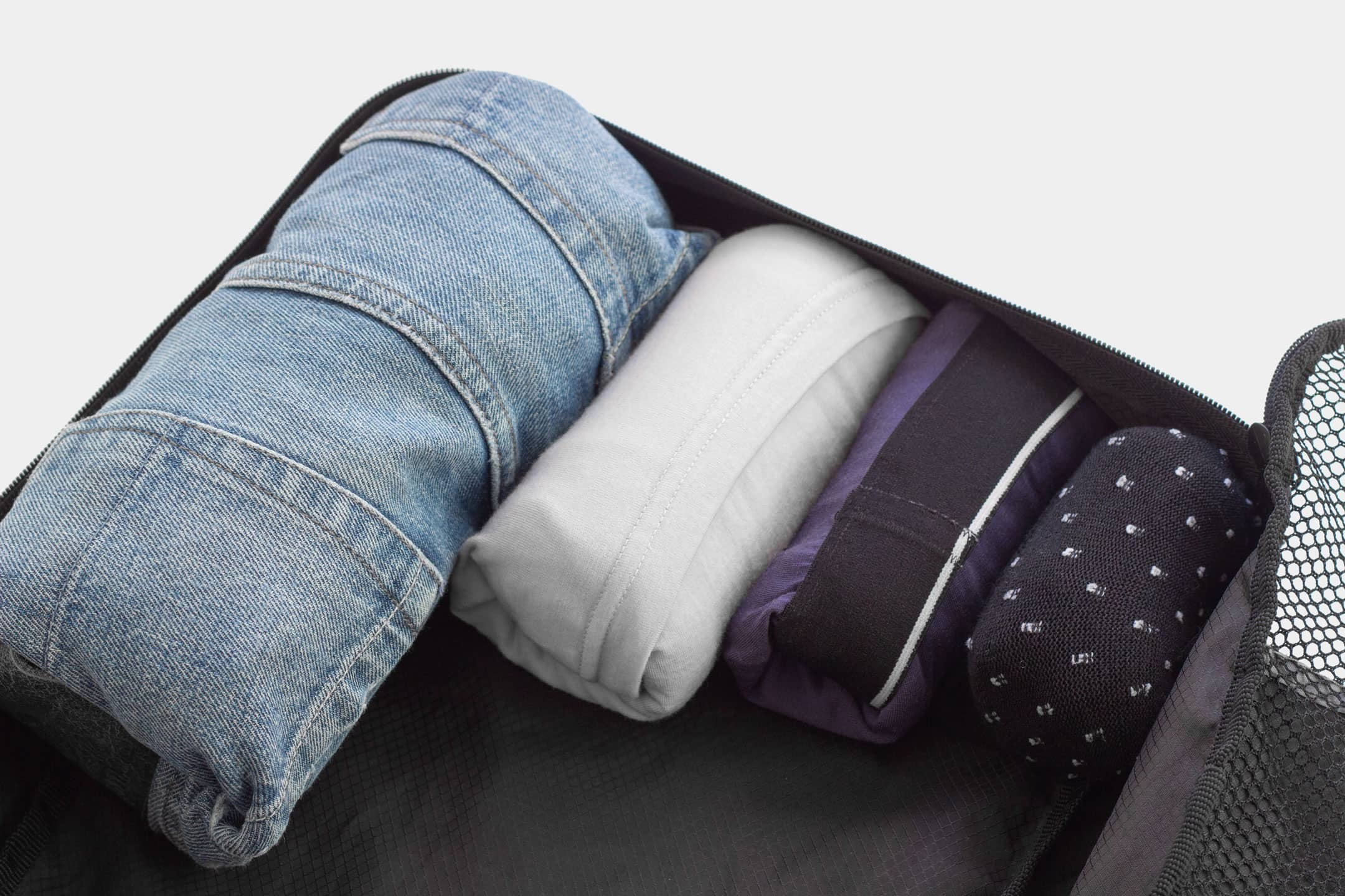 Rolled clothes nestled in a packing cube