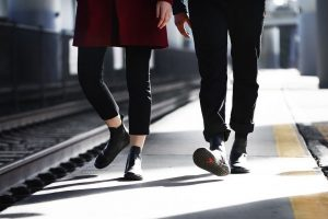 Stylish couple walking along train tracks